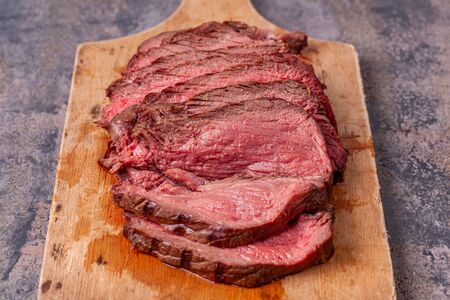 Roast beef slices on wooden cutting board on grey marble background