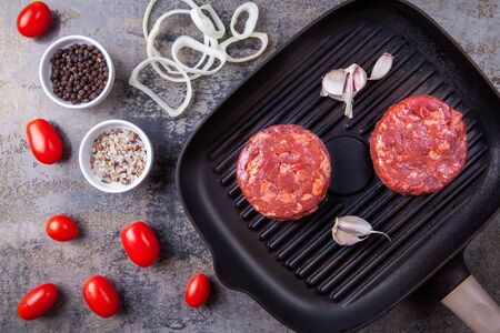 Ready to cook raw beef burger meats with garlic on grill pan, tomatos and onion