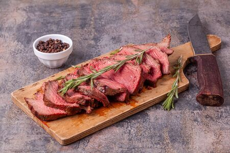 Slices of medium rare roast beef meat on wooden cutting board, old knife, pepper Reklamní fotografie