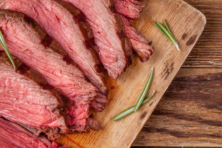 Close up of roast beef on wooden cutting board with rosemary Reklamní fotografie