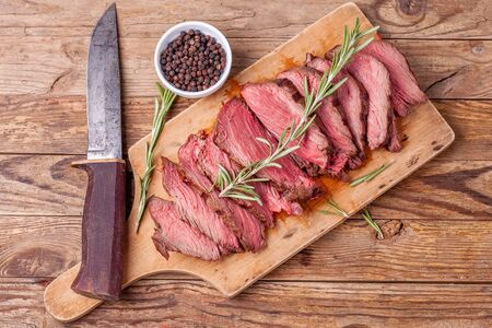 Sliced medium rare roasted beef meat on wooden cutting board, hunters knife Reklamní fotografie