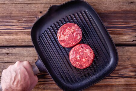 Mans hand holding grill pan with raw beef burger meats on a wooden background