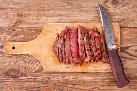 Slices of roast beef meat on wooden cutting board with old knife. Top view.