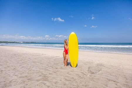 Cute young woman in red swimsuit with surfboard alone on the beach with waves