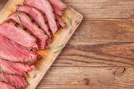 Slices of medium rare roast beef meat on wooden cutting board. Copy space.
