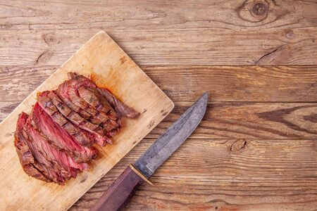 Slices of medium rare roast beef meat on wooden cutting board, knife. Copy space