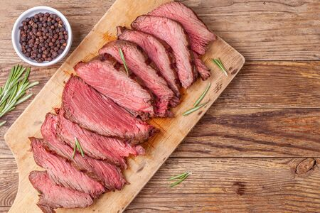 Sliced medium rare roast beef meat on wooden cutting board, pepper and rosemary Reklamní fotografie