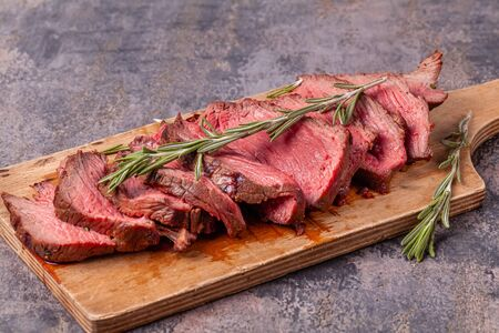 Slices of medium rare roast beef meat on wooden cutting board and rosemary twigs