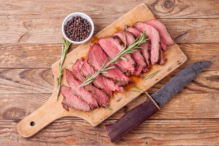 Slices of medium rare roast beef meat on wooden cutting board, hunters knife