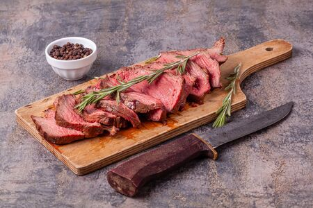 Slices of medium rare roast beef meat on wooden cutting board, old knife, pepper Stock fotó
