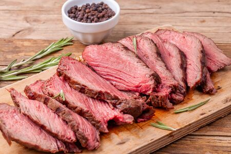 Close up slices of medium rare roast beef on wooden cutting board with rosemary