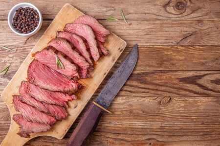 Slices of medium rare roast beef meat on wooden cutting board and hunters knife