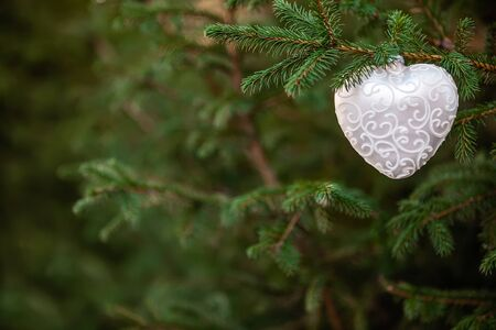 Close-up of Christmas decoration toy shaped like a heart, green wood background