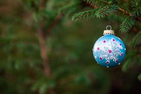 Close-up of Christmas decoration ball toy hanging on fir tree branch, copy space 写真素材