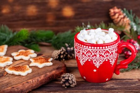Christmas New Year holidays concept. Red cup with ornament with hot cocoa and marshmallows, toasted shaped bread slices in winter decorations on wooden table. Stock Photo