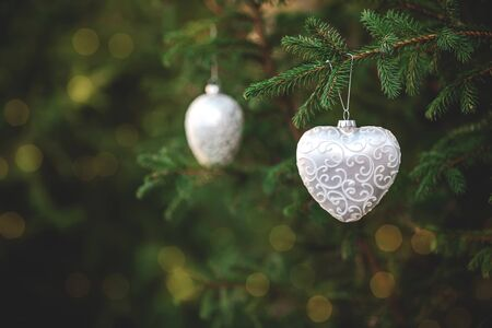 Christmas spruce decoration toys shaped like a heart hanging on a tree branch with bokeh blurred lights. Green wood background. Copy space. Concept of outdoor New Year holiday.
