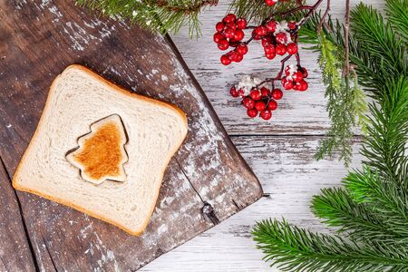 Slice of toast bread with a toasted cut out shaped like a fir tree on a vintage rustic wooden cutting board in winter holidays decorations. Concept of Christmas and New Year breakfast food.