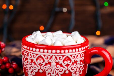Close up of red mug with ornament with hot cocoa drink and white sweet marshmallows with garland bokeh lights background. Christmas and New Year holidays concept.