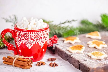 Cold season concept. Red cup with hot chocolate and cute marshmallows, cinnamon sticks, anise stars, toasted shaped bread slices on wooden table in winter decorations. Christmas New Year celebration Stok Fotoğraf