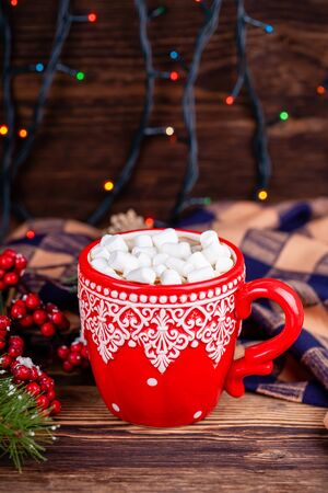Red cup with winter ornament with hot cocoa drink and sweet marshmallows on wooden table with plaid in Christmas decorations with garland bokeh lights background. New Year holidays concept.