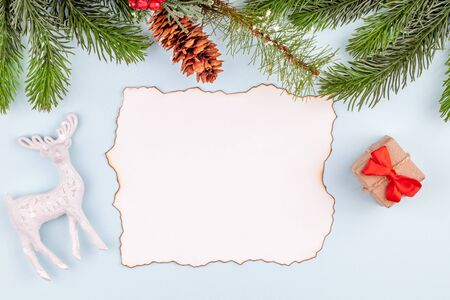 Empty greeting card paper with burnt edges in Christmas decorations - handmade gift box with red bow, toy deer and pine tree branches. Concept of New Year and Xmas celebration card. Copy space.