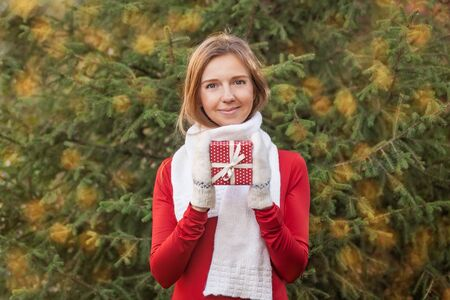 Attractive happy young woman with Christmas gift box, fir tree bokeh background Фото со стока