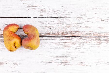 Ugly fruits pair of ripe pears on white wooden table background with copy space