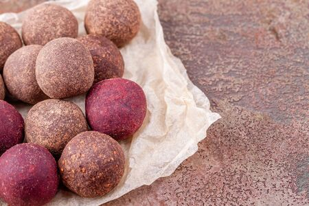 Close Up of Homemade Vegan Cocoa Energy Balls on Craft Paper on Brown Background
