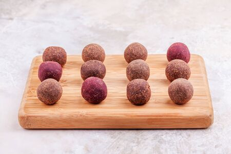 Homemade Raw Vegan Cacao Energy Balls on Wooden Tray on White Marble Background