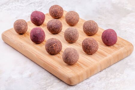 Homemade Raw Vegan Cacao Energy Balls on Wooden Tray on White Marble Background. Healthy Chocolate Sweets from Nuts and Dates. Concept of Natural Vegetarian Handmade Dessert Stock Photo