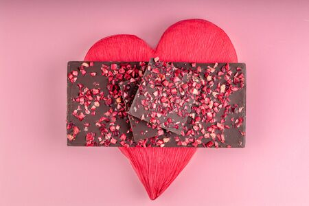Chocolate with Pieces of Dried Berries Lies a Stack on Red Heart 스톡 콘텐츠