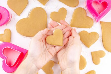 Woman Hands Holding the Raw Heart Shaped Cookie
