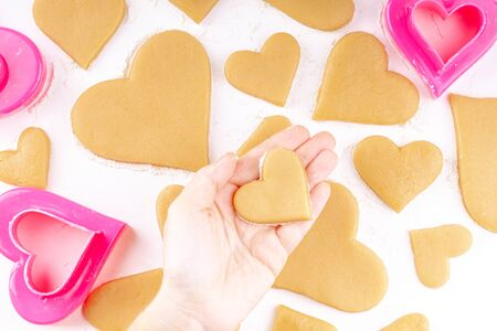 Woman Hand Holding the Raw Heart Shaped Cookie with a Lot of Homemade Cookies with Pink Cookie Cutter and Flour on Background. Concept of Happy Valentines Day and Birthday. Top View Reklamní fotografie