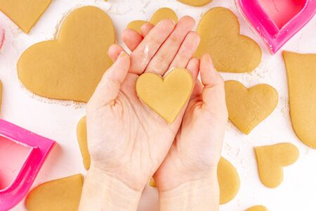 Woman Hands Holding the Raw Heart Shaped Cookie with a Lot of Homemade Cookies with Pink Cookie Cutter and Flour on Background. Concept of Happy Valentines Day and Birthday. Top View