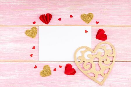 Valentines Day, Birthday Composition. Blank White Greeting Card with Handmade Paper Hearts, Confetti and Wooden Gold Heart on Pink Wooden Background. Valentines Day Concept. Top View, Copy Space