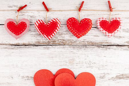 Valentines Background with Handmade Sewed Pillow Hearts Row Border with Red Pins on Jute Rope and Two Wooden Hearts at Rustic White Wood Background. Concept of Happy Valentine's Day. Copy Space