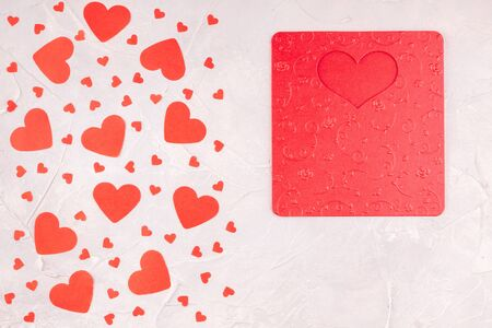 Valentines Background with Red Embossing Valentine Card and Confetti Paper Hearts on Concrete Gray Background. Love, Romance, Happy Valentines Day Concept. Top View