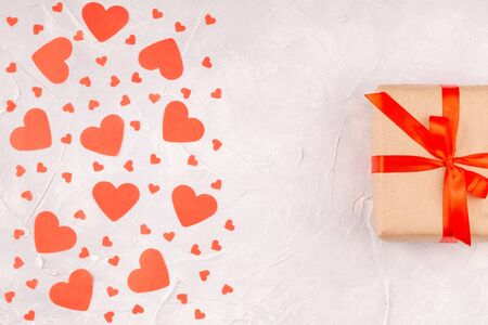 Gift Box with Red Ribbon Bow and Confetti Paper Hearts on Concrete Background Reklamní fotografie