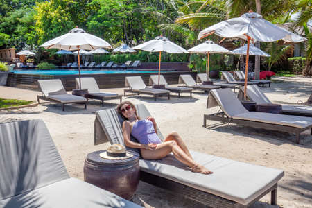 Beautiful Woman Relax and Sunbathing on Vacation in Resort with Pool and Sunbeds