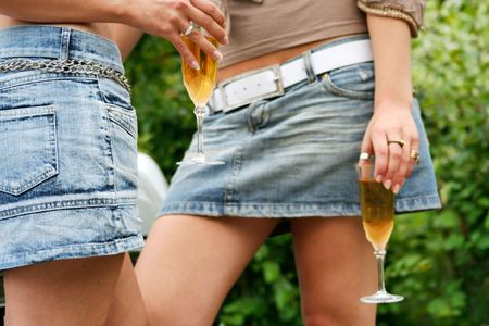 jeans skirt: Two young girls grinking alcohol Stock Photo