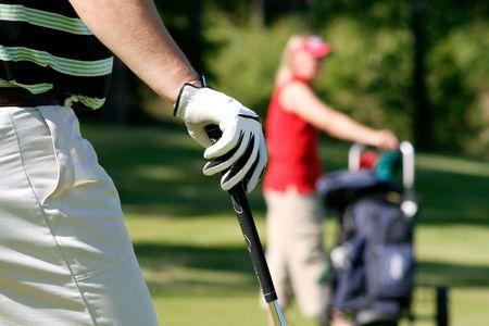 golfers: Couple playing golf