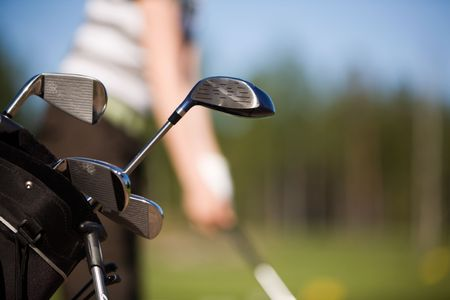 freetime: Young golfer practising at range, focus on clubs Stock Photo