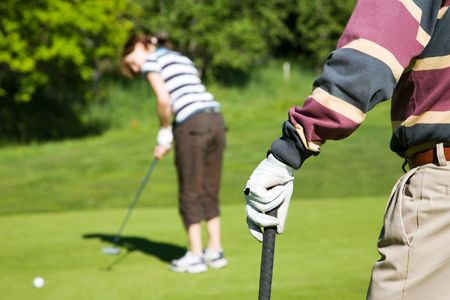 junior: Senior man playing golf with his grandaughter Stock Photo
