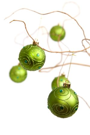 Green christmas baubles hanging from golden curly branches Stock Photo