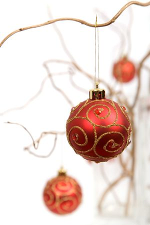 Red christmas baubles hanging from golden curly branches