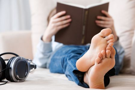 girl feet: Teenager reading on the couch Stock Photo