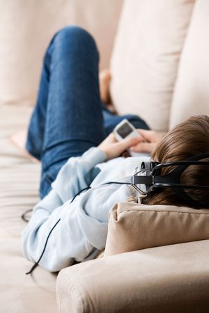 Teenager listening music on the couch photo