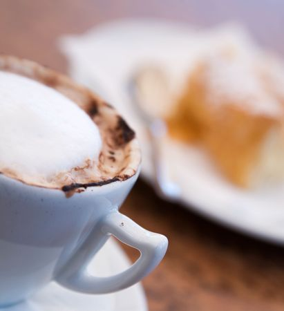 Cappuccino and delicious pastry on cafe table