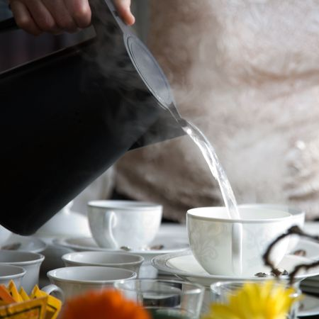 steaming: Woman pouring hot water to fancy tea cups