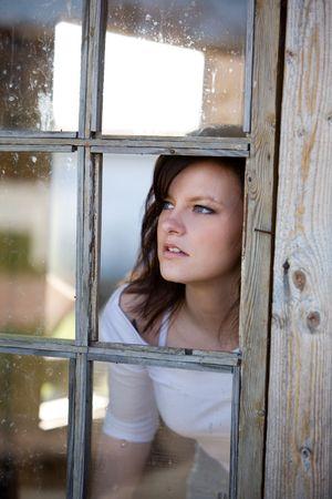 Woman looking outside from broken window photo